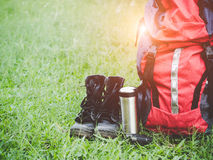Hiking travel gear on glasses. Items include hiking boots, cup, map,binoculars. Royalty Free Stock Photos