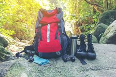 Hiking travel gear on glasses. Items include hiking boots, cup, map,binoculars. Flat lay of outdoor travel equipment items for royalty free stock photos