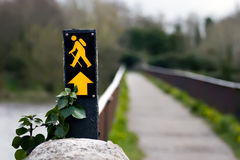 Hiking/trekking sign with unfocused bridge. Hiking/trekking sign with out of focus food bridge in background in landscape view Royalty Free Stock Photo