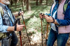 Hiking with trekking sticks. Senior men and women hiking with trekking sticks in the forest, close-up view with cropped face stock images