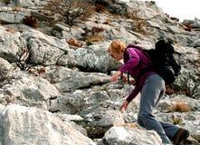 Hiking up the rocky mountain. Elegant woman hiker climbing up on dangerous rocky terrain Stock Photo