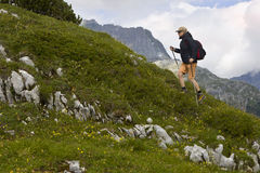 Hiking uphill. Mature woman hiking uphill in The Alps royalty free stock images