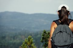 Hiking uphill a mountain. Woman with backpack and cap. royalty free stock photos