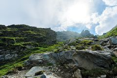 Hiking uphill rocky slopes of fagaras mountains. Hard path among big and sharp boulders. sunny summer weather with cloudy sky royalty free stock photo