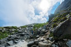Hiking uphill rocky slopes of fagaras mountains. Hard path among big and sharp boulders. sunny summer weather with cloudy sky royalty free stock photography