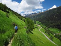 Hiking walking backpacking trekking Alps South Tyrol Italy. Walkers follow the path of a narrow stream towards snow-capped Alpine peaks in the South Tyrol region Royalty Free Stock Image
