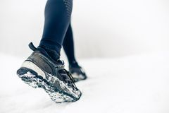 Hiking or walking shoes on snow, winter mountains. People power walking on snow, white winter day. Female hiker on winter adventure. Sport, fitness Royalty Free Stock Photos