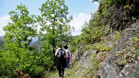 Hiking walking on trail. Healthy lifestyle hiker people walking in mountains. Young woman and children hikers on mountain path