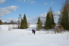 Hiking in winter. Two men with backpacks go on snow in solar winter day royalty free stock photography