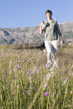 Hiking woman. In a meadow in the mountains with a mountain shelter in the background - Seiser Alm - Dolomites Royalty Free Stock Photography