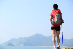 Hiking woman seaside. Back of hiking woman stand on seaside rock Stock Images