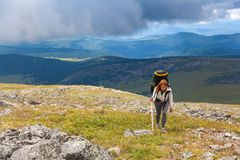 Hiking woman with backpack. Atmospheric moment in mountains. Hiking woman with backpack traveler on top of mountains. Stylish woman hiking, in the background a stock images