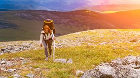 Hiking woman with backpack. Atmospheric moment in mountains. Hiking woman with backpack traveler on top of mountains. Stylish woman hiking, in the background a royalty free stock images