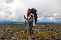 Hiking woman with backpack. Atmospheric moment in mountains. Hiking woman with backpack traveler on top of mountains. Stylish woman hiking, in the background a stock photo