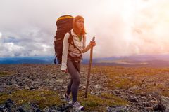 Hiking woman with backpack. Atmospheric moment in mountains. Hiking woman with backpack traveler on top of mountains. Stylish woman hiking, in the background a stock photography