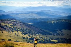 Hiking woman with backpack. Atmospheric moment in mountains. Hiking woman with backpack traveler on top of mountains. Stylish woman hiking, in the background a Royalty Free Stock Photography