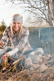 Hiking woman with backpack cook by campfire. Young hiking woman with backpack cook on campfire in countryside Royalty Free Stock Image