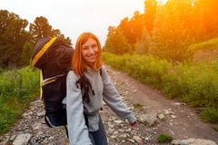 Hiking woman with backpack. Cheerfully smiles, enjoys a hike in the mountains.Hipster traveler on top of forest, amazing view. Wanderlust fun and travel concept royalty free stock images