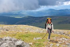 Hiking woman with backpack. Cheerfully smiles, enjoys a hike in the mountains.Hipster traveler on top of forest, amazing view. Wanderlust fun and travel concept stock photography