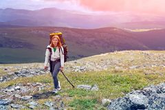 Hiking woman with backpack. Cheerfully smiles, enjoys a hike in the mountains.Hipster traveler on top of forest, amazing view. Wanderlust fun and travel concept stock photos