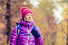 Hiking woman with backpack looking at camera in inspirational au. Hiking woman with backpack looking at inspirational autumn golden trees and woods. Fitness Stock Photography