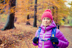 Hiking woman with backpack looking at camera in inspiring autumn Royalty Free Stock Photos