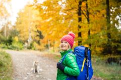 Hiking woman with backpack looking at inspirational autumn golde. Hiking woman with backpack looking at camera and inspirational autumn golden woods. Fitness stock photo