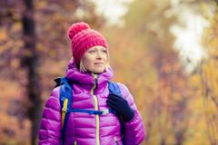 Hiking woman with backpack looking at inspirational autumn golde Stock Photography