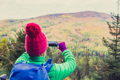 Hiking woman with backpack taking photo with smartphone Royalty Free Stock Photography