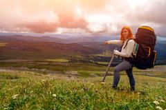 Hiking woman with backpack. Travel Lifestyle and survival concept rear view. Hiking woman with backpack enjoying the trekking and showing the hand direction of stock photography