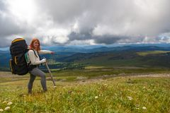 Hiking woman with backpack. Travel Lifestyle and survival concept rear view. Hiking woman with backpack enjoying the trekking and showing the hand direction of royalty free stock photography