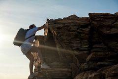 Hiking woman climb to hill submit. Hiking woman climbing up to top hill summit during sunset. Professional female climber to mountain peak at sunset. Outdoor Stock Photo