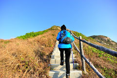 Hiking woman climbing mountain stairs Stock Image