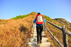 Hiking woman climbing stairs on mountain. Hiking woman climbing the stone stairs to mountain peak Royalty Free Stock Photo