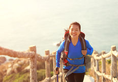 Hiking woman climbing up to mountain peak. Hiking asian woman climbing up on mountain stairs Stock Photography