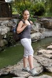 Hiking woman cross river with travel bag Stock Photo