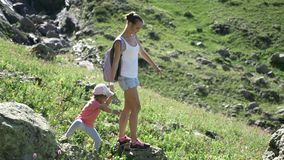 Hiking woman with daughter on travel excursion walking in mountain landscape. stock video