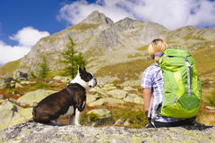 Hiking woman with dog in mountains Stock Images
