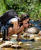 Hiking woman drinking water with hands from stream Stock Photography