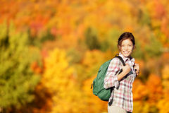 Hiking woman in Fall forest. Female hiker looking around in forest in autumn colors. Beautiful young woman on hike Stock Photo