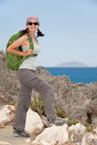 Hiking woman. Female tourist standing on a rock against the sea Royalty Free Stock Photography