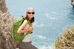 Hiking woman. Female tourist standing on a rock against the sea Stock Image