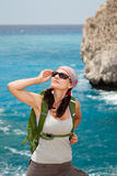 Hiking woman. Female tourist standing on a rock against the sea Royalty Free Stock Photo