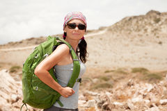 Hiking woman. Female tourist standing on a rock against the sea Stock Photo