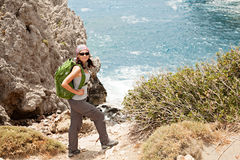Hiking woman. Female tourist standing on a rock against the sea Stock Photography
