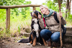 Hiking woman with her dog on a trail. Hiking woman with rucksack and her bernese mountain dog on a trail Stock Photo