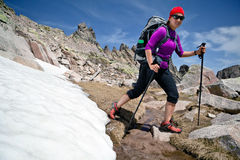 Hiking woman in mountains with snow. Hiking woman in rocky mountains with snow. Trekking with backpack in sunny Corsica, France Stock Image