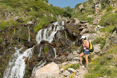 Hiking woman next to waterfall in the mountains Royalty Free Stock Photos