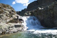 Hiking woman next waterfall Royalty Free Stock Photography