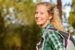 Hiking woman portrait smiling happy in forest. Female hiker girl. Trekking wearing backpack outside looking candid and fresh at camera. Beautiful young blonde Stock Images